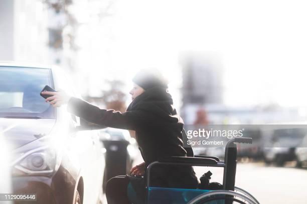 woman in wheelchair using cellphone as remote control - sigrid gombert imagens e fotografias de stock