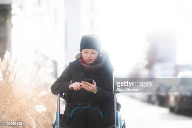 woman in wheelchair using cellphone in street - sigrid gombert fotografías e imágenes de stock