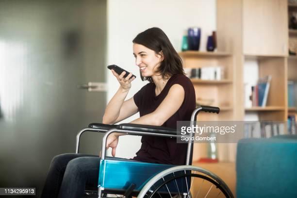 woman in wheelchair using cellphone - sigrid gombert stock-fotos und bilder