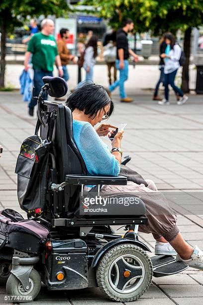 Femme dans un fauteuil roulant à l'aide de téléphone portable à Oslo rue, Norvège