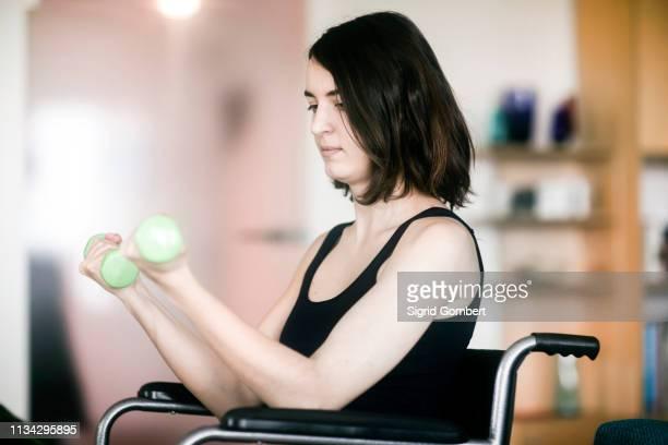 woman in wheelchair using weights at home - sigrid gombert stock-fotos und bilder