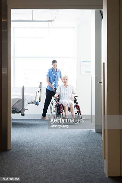 Woman in wheelchair with nurse, view through open door