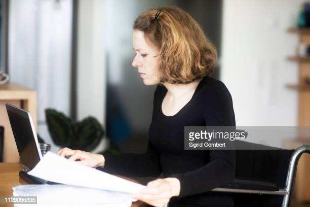 woman in wheelchair working at laptop - sigrid gombert stock-fotos und bilder