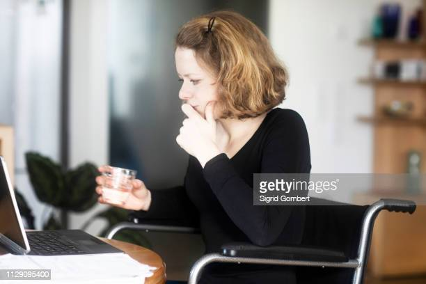 woman in wheelchair working at laptop - sigrid gombert stock pictures, royalty-free photos & images