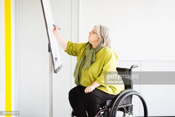 woman in wheelchair working in office