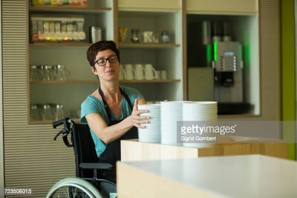 woman in wheelchair, working in restaurant, stacking bowls - sigrid gombert fotografías e imágenes de stock