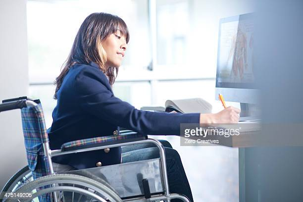 Woman in wheelchair writing notes