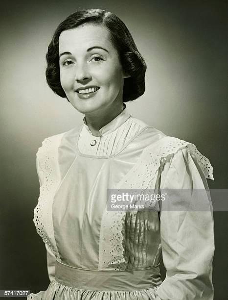 Woman in white apron posing in studio, (B&W), (Portrait)