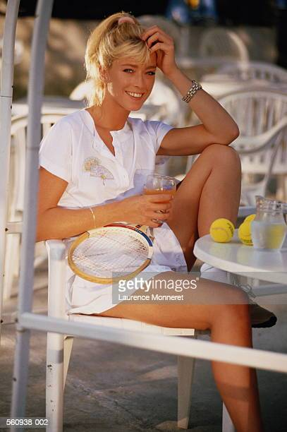 Woman in white at table drinking fruit juice after game of tennis
