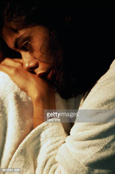 woman in white bathrobe curled up and looking pensive - sexual violence stock pictures, royalty-free photos & images