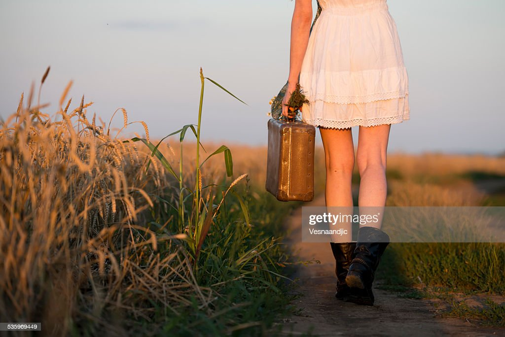 Woman in white dress and boots holding suitcase walking : Stock Photo