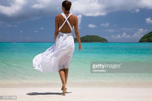 Donna in abito bianco sulla spiaggia