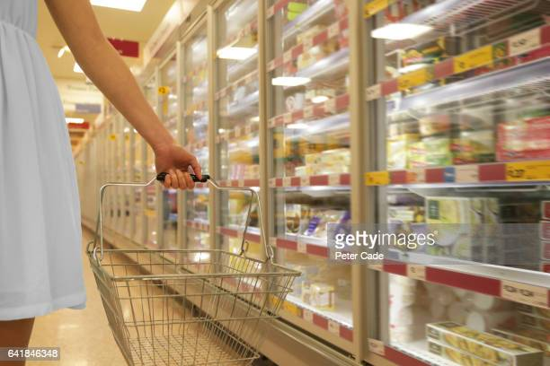 Woman in white dress holding shopping basket in supermarket