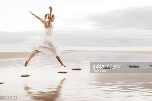 Woman in white dress jumping over stepping stones