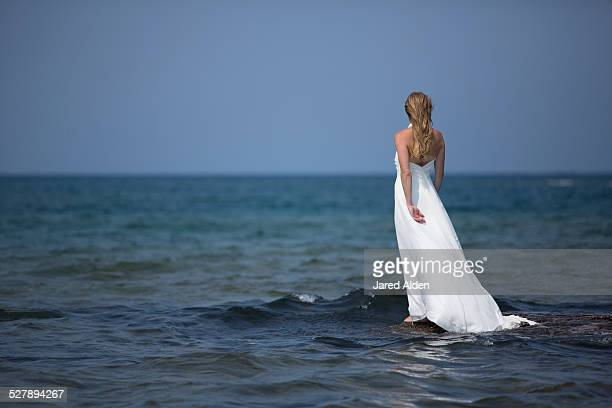 woman in white dress on rock admits blue water - long dress stock pictures, royalty-free photos & images