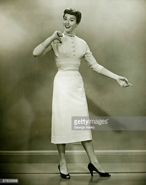 Woman in white dress pointing to herself in studio, (B&W), portrait