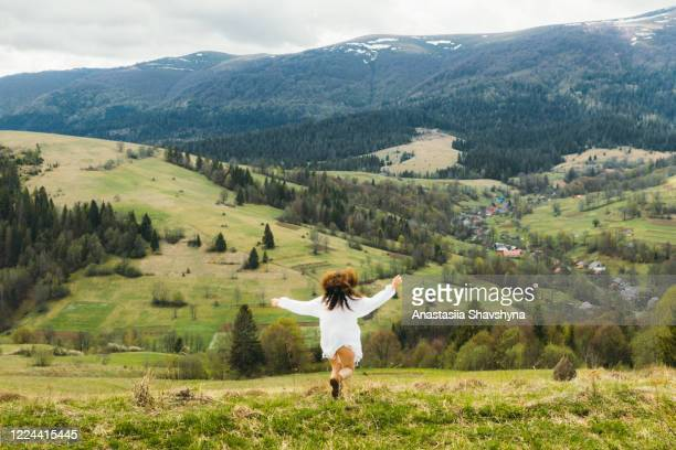 woman in white dress running through the wind and sun in the mountains - ukraine stock pictures, royalty-free photos & images