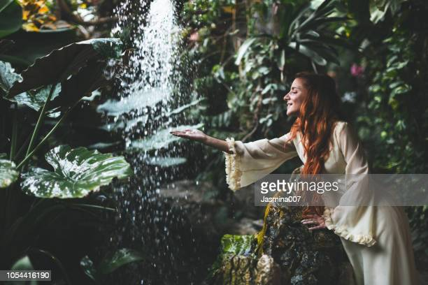 woman in white dress standing against waterfall - wilderness area stock pictures, royalty-free photos & images