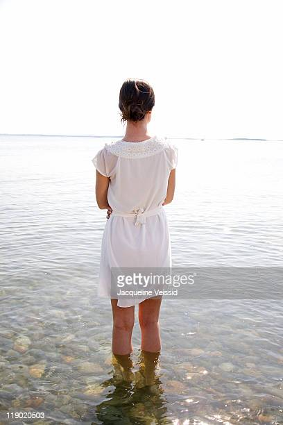Woman in white dress standing in water (rear view)