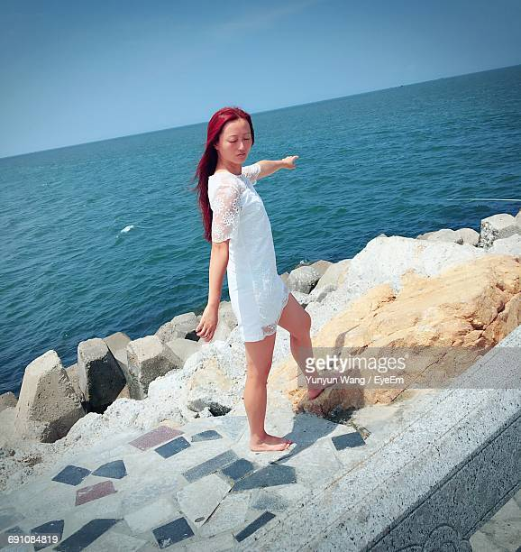 Woman In White Dress Standing On Groyne By Sea Against Clear Sky