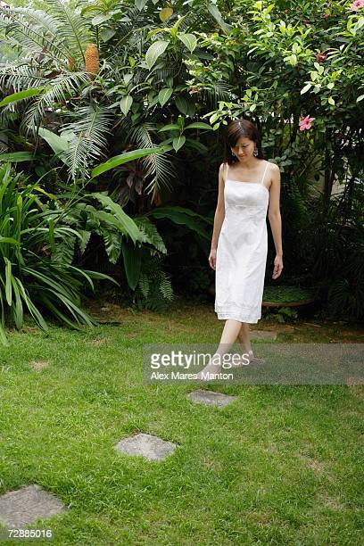 woman in white dress stepping on stones in garden - 白のドレス ストックフォトと画像