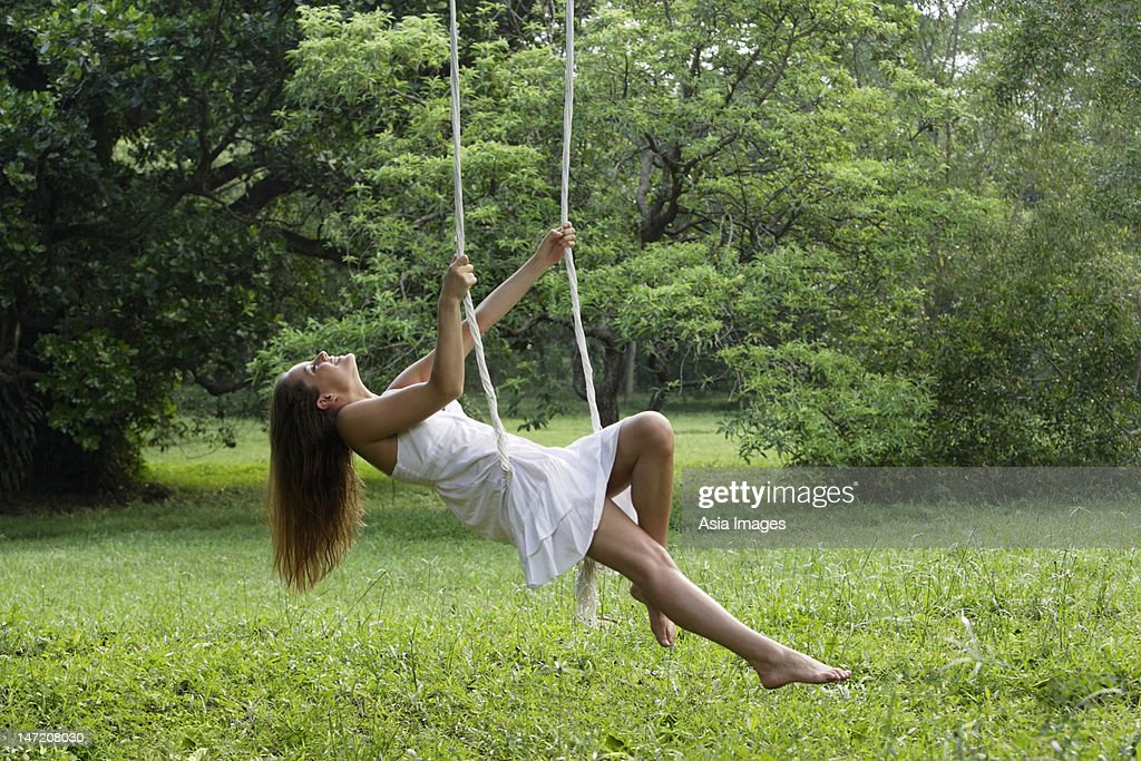 https://media.gettyimages.com/photos/woman-in-white-dress-swinging-in-tree-swing-picture-id147208030