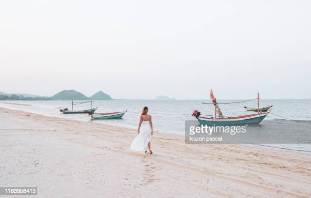 woman in white dress walking alone on the beach during a summer day . - 白のドレス ストックフォトと画像