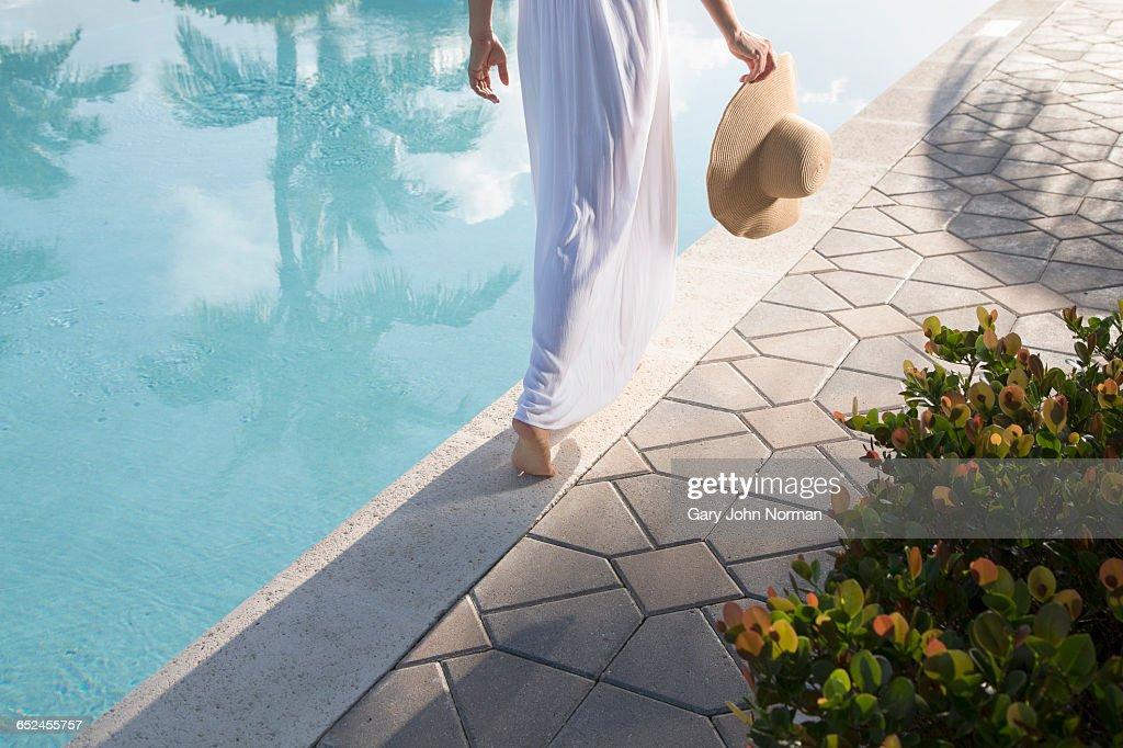 Woman in white dress walking close to pool edge : Stock Photo