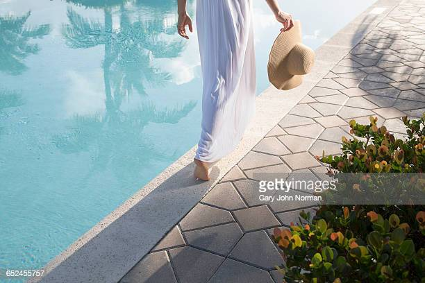 woman in white dress walking close to pool edge - health farm stock pictures, royalty-free photos & images