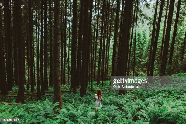 Woman in white dress walking in the forest