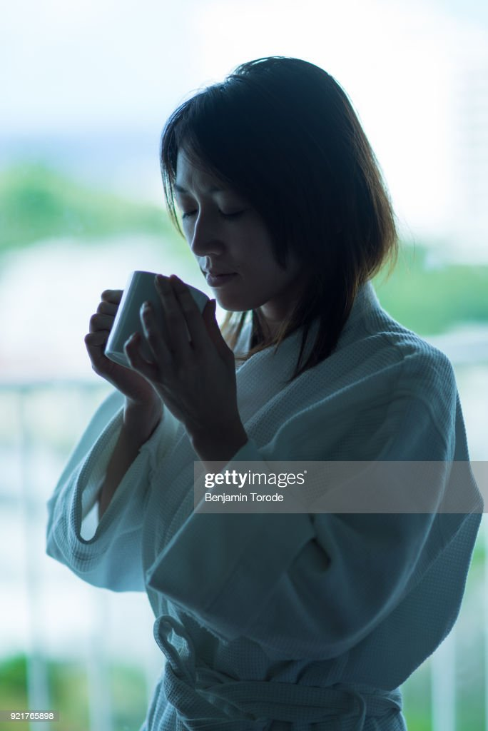 Woman In White Dressing Gown Smelling Cup Of Coffee Stock Photo ...