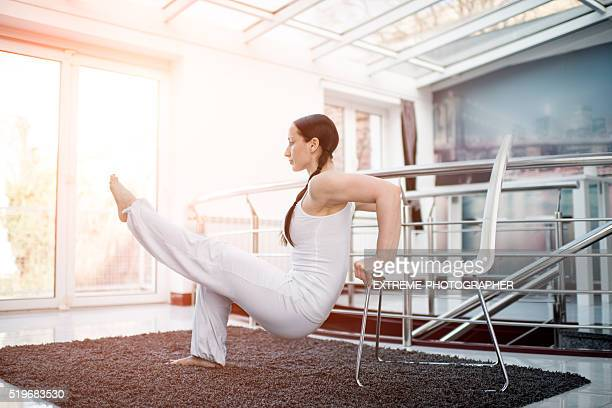 Woman in white exercising with a chair