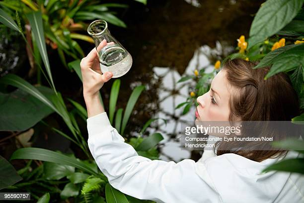 woman in white holding a beaker of clear liquid - ecologist stock pictures, royalty-free photos & images