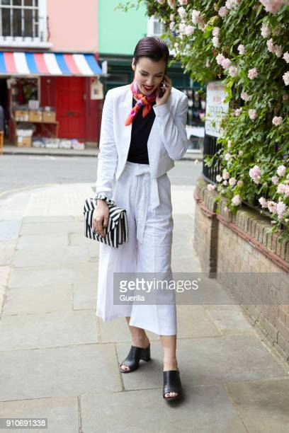 Woman in white linen suit using phone in street, full length