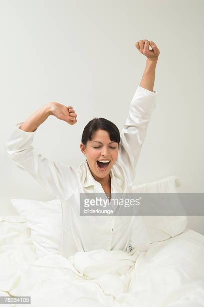 woman in white pajamas yawning in her bed in the morning