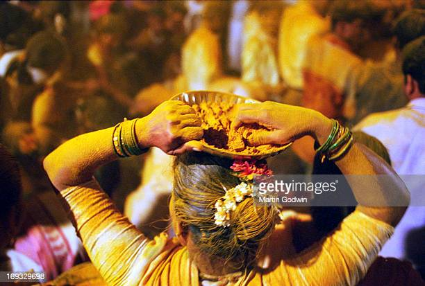 Woman in white sari at Hindu festival throwing powdered yellow turmeric and chunks of coconut over revellers from a basket on her head her arms...