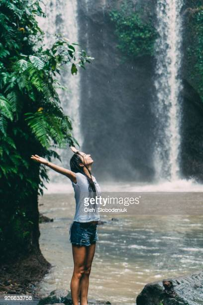 woman  in white shirt standing near  tibumana   waterfall under the rain  in bali, indonesia - wet shirt stock photos and pictures