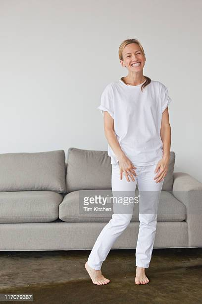Woman in white standing in apartment, smiling