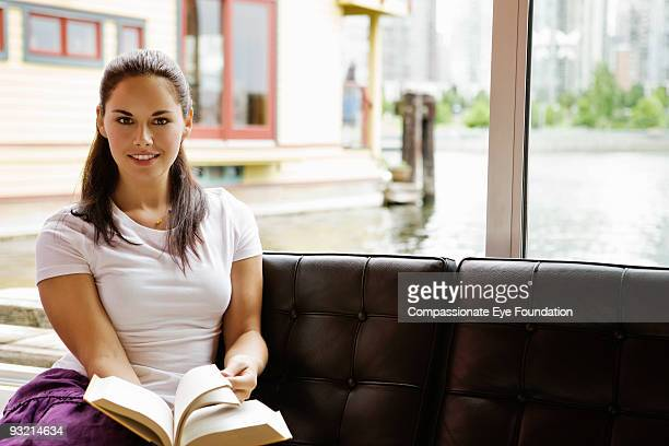 woman in white tshirt holding book