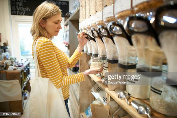 woman in whole foods refill store dispensing oats into jar. - merchandise stock pictures, royalty-free photos & images