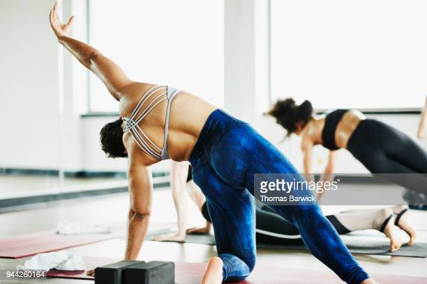 woman in wild thing pose during hot yoga class in fitness studio - sports bra stock pictures, royalty-free photos & images
