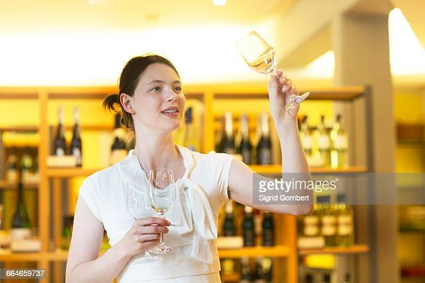 woman in wine shop holding up wine glass checking cleanliness - sigrid gombert stockfoto's en -beelden
