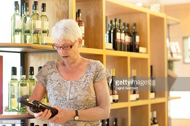 woman in wine shop selecting bottle of wine - sigrid gombert stock-fotos und bilder