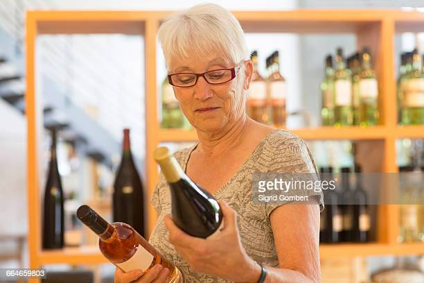 woman in wine shop selecting bottle of wine - sigrid gombert stock pictures, royalty-free photos & images