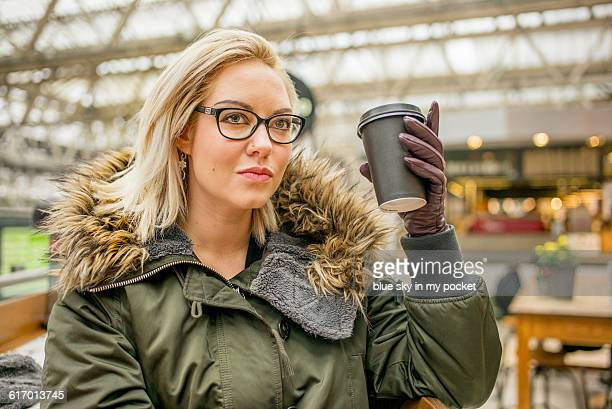 A woman in winter clothes drinking coffee