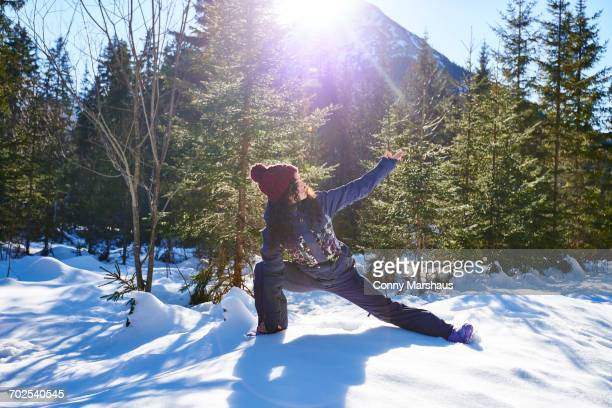 Woman in winter clothes practicing side angle yoga pose in snowy forest, Austria