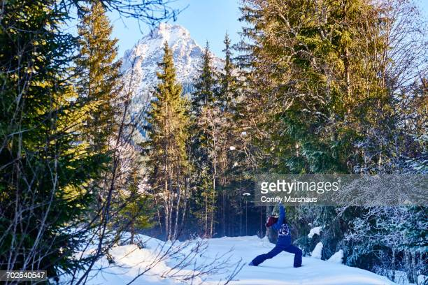Woman in winter clothes practicing warrior yoga pose in snowy forest, Austria