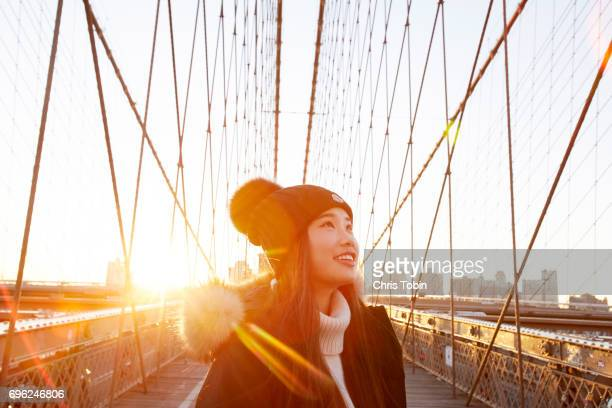 woman in winter clothing smiling and looking up with sun in background on brooklyn bridge - finding stock photos and pictures