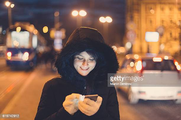 Woman in winter clothing texting at the street