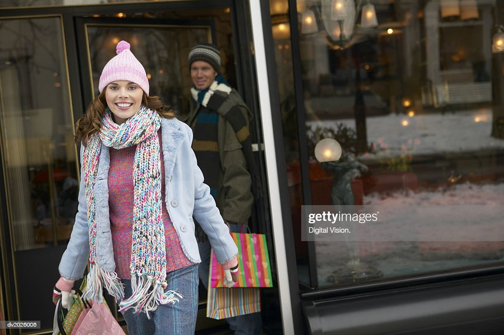 Woman in Winter Clothing Walks Out of a Shop Carrying Shopping Bags, Her Boyfriend in the Background : Stock Photo